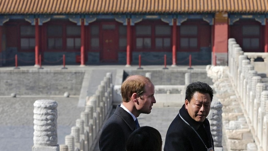 Britain's Prince William, left, chats with Chinese officials as he tours the Forbidden City in Beijing Monday, March 2, 2015. William presented China's president with a large envelope Monday containing an invitation from the queen to visit Britain this year, as he began the first official visit to mainland China by a senior British royal in a generation. (AP Photo/Andy Wong, Pool)