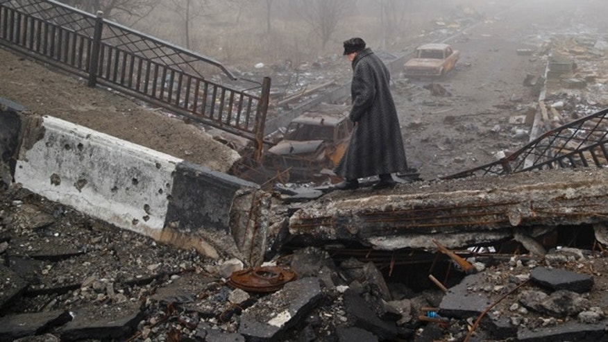 March 1, 2015: An elderly woman walks across a destroyed bridge, fallen onto the road towards the airport, the scene of heavy fighting in Donetsk, Ukraine.  (AP Photo/Vadim Ghirda)