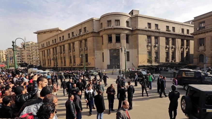 People gather the site of a bomb blast in front of the Egyptian High Court, in Cairo, Egypt, Monday, March 2, 2015. Egyptian state TV says a midday bomb blast in downtown Cairo wounded several people. Egypt has seen a series of attacks mainly targeting security forces since the military ousted Islamist President Mohammed Morsi in the summer of 2013. The attacks have raised fears ahead of an economic conference later this month aimed at attracting foreign investment. (AP Photo/Amr Nabil)