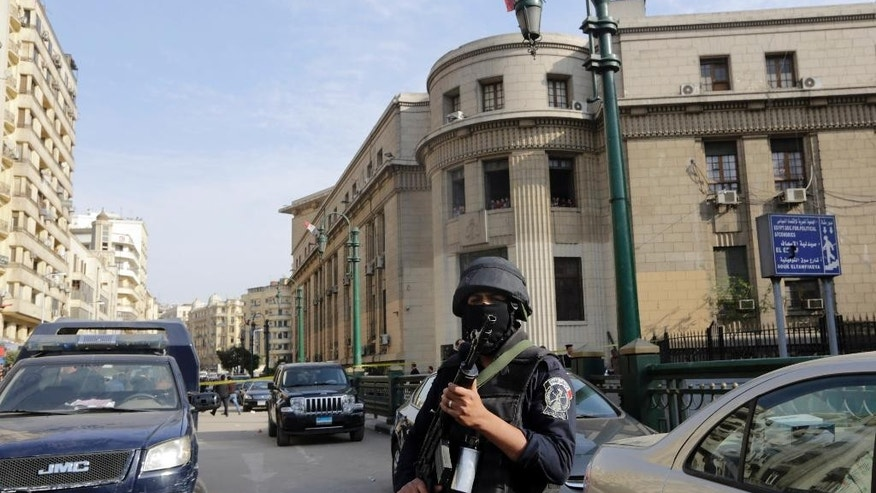 An masked policemen stands alert at the site of a bombing in front of the Egyptian High Court, in Cairo, Egypt, Monday, March 2, 2015. Egyptian state TV says the midday bomb blast in downtown Cairo wounded several people. Egypt has seen a series of attacks mainly targeting security forces since the military ousted Islamist President Mohammed Morsi in the summer of 2013. The attacks have raised fears ahead of an economic conference later this month aimed at attracting foreign investment. (AP Photo/Amr Nabil)