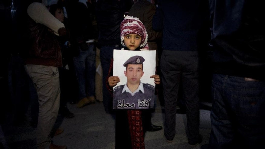 "FILE - In this Feb. 2, 2015 file photo, a Jordanian child holds a poster with a picture of Jordanian pilot, Lt. Muath al-Kaseasbeh, who is held by the Islamic State group militants, with Arabic that reads, ""we are all Muath,"" in Amman, Jordan. How rooted in Islam is the ideology embraced by the Islamic State group that has inspired so many to fight and die? The group has assumed the mantle of Islam's earliest years, claiming to recreate the conquests and rule of the Prophet Muhammad and his successors. But in reality its ideology is a virulent vision all its own, one that its adherents have plucked from centuries of traditions. (AP Photo/Nasser Nasser, File)"