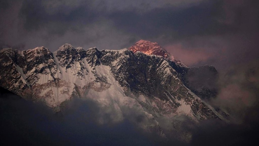 FILE - In this Oct. 27, 2011 file photo, the last light of the day sets on Mount Everest as it rises behind Mount Nuptse as seen from Tengboche, in the Himalaya's Khumbu region, Nepal. Human waste left by climbers on Mount Everest has become a problem that is causing pollution and threatening to spread disease on the world's highest peak, chief of Nepal's mountaineering association said Tuesday, March 3, 2015. Ang Tshering told reporters Tuesday that the more than 700 climbers and guides who spend nearly two months on Everest's slopes each climbing season leave large amounts of feces and urine, and the issue has not been addressed. He said Nepal's government needs to get the climbers to dispose of the waste properly so the mountain remains pristine. (AP Photo/Kevin Frayer, File)
