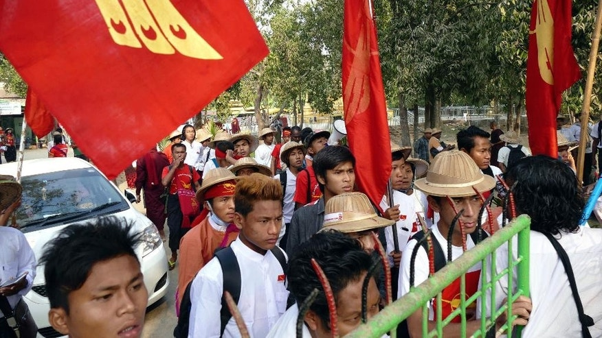 """Student protesters wait near the gate of Aung Mye Beikman monastery after police surrounded the monastery apparently to prevent them from proceeding with a protest march to Yangon from Letpadan, north of Yangon, Myanmar, Monday, March 2. 2015. Student protesters who are marching from Myanmar's second largest city of Mandalay to old capital Yangon continued their trek Monday after suspending it for ten days. Myanmar's government warned student protesters last month against marching to Yangon to seek educational reforms, saying """"action will be taken"""" to restore law and order if they go ahead. (AP Photo/Khin Maung Win)"""