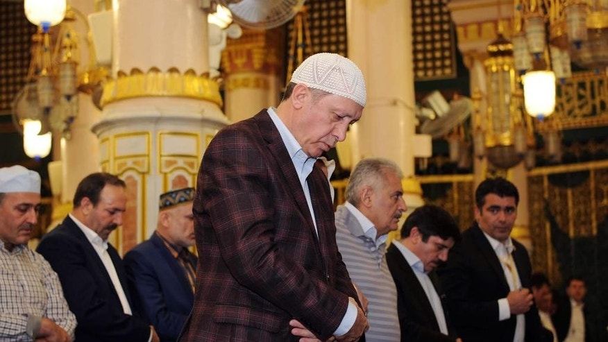 In this photo provided by the Saudi Press Agency, Turkey's President Recep Tayyip Erdogan, center, prays at the Prophet Mohammed Mosque, the second holiest site in Islam, in the Saudi holy city of Medina, Monday, March 2, 2015. Saudi King Salman is scheduled to meet Monday with Erdogan. (AP Photo/SPA)