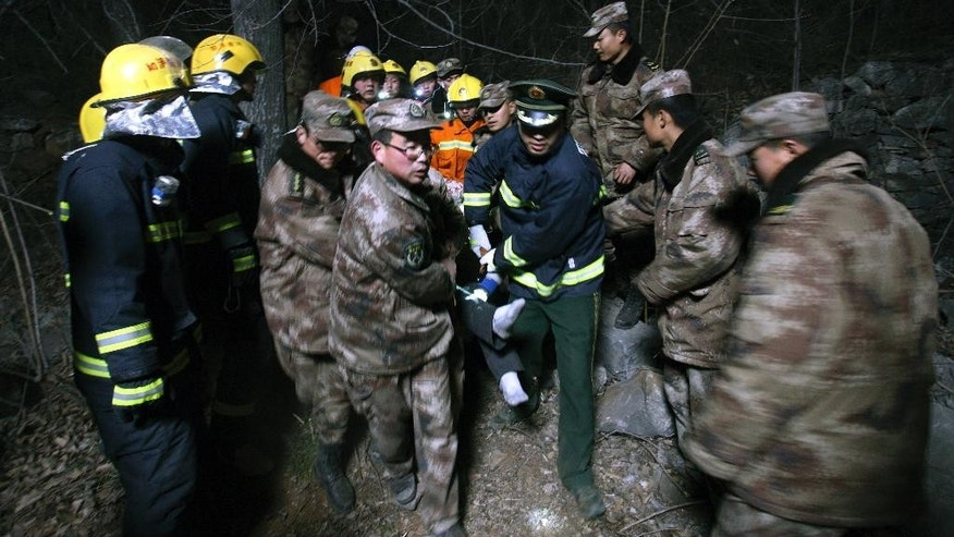 Rescuers carry an injured person from a bus accident site in Linzhou in central China's Henan province Tuesday, March 3, 2015. A bus carrying an opera troupe fell off a cliff on Tuesday, killing and injuring more than a dozen people, state media reported. (AP Photo) CHINA OUT
