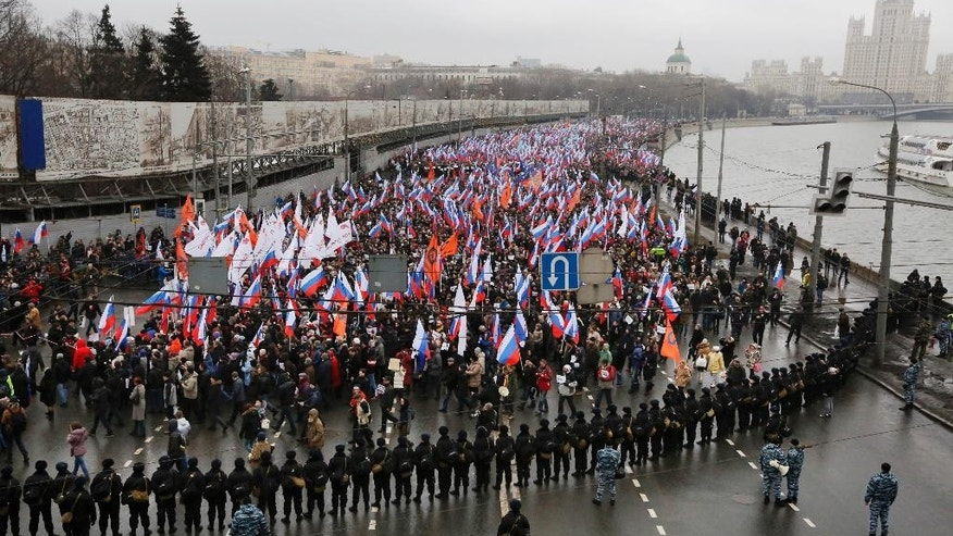 "People carry Russian national flags during a march in memory of opposition leader Boris Nemtsov who was gunned down on Friday, Feb. 27, 2015 near the Kremlin, in Moscow, Russia, Sunday, March 1, 2015. Thousands converged Sunday in central Moscow to mourn veteran liberal politician Boris Nemtsov, whose killing on the streets of the capital has shaken Russia's beleaguered opposition. They carried flowers, portraits and white signs that said ""I am not afraid.""  (AP Photo/Dmitry Lovetsky)"