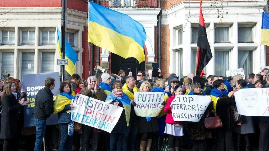 "Ukrainian protesters stand outside the Russian Embassy in central London, Sunday, March 1, 2015,  after the shooting of Russian opposition politician Boris Nemtsov in Moscow. Nemtsov was gunned down shortly before midnight Friday as he walked across a bridge near the Kremlin. The killing came just hours after a radio interview in which he denounced Putin's ""mad, aggressive policy"" in Ukraine. (AP Photo/PA,  Laura Lean)  UNITED KINGDOM OUT"