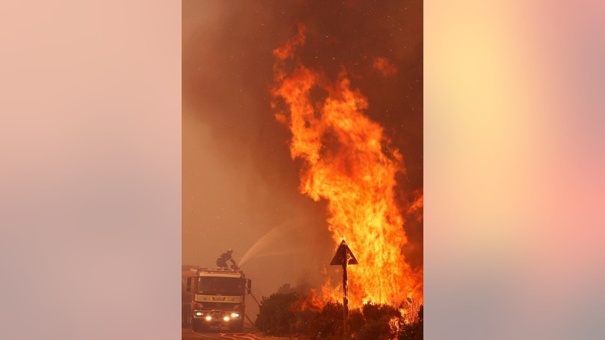 Fire fighters, left, battle a fire near the town of Hout Bay, South Africa, Monday, March 2, 2015.  South African firefighters say they are battling to control a wildfire that has burned down five homes in Cape Town's southern peninsula. Spokeswoman Liezl Moodie said Monday that nearly 150 firefighters, along with park volunteers, have combated the blaze since early Monday.  (AP Photo/Schalk van Zuydam)