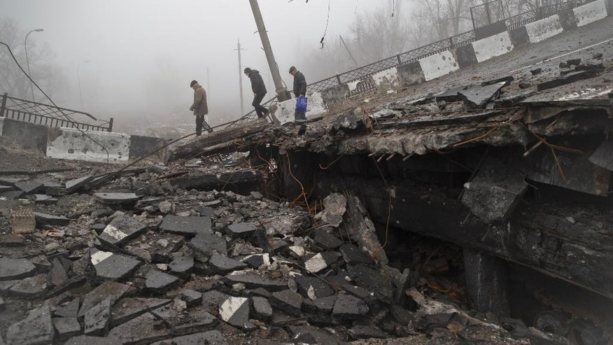 Men across a destroyed bridge, fallen onto the road towards the airport, the scene of heavy fighting in Donetsk, Ukraine, Sunday, March 1, 2015.  The recent pullback of some weapons from the line separating government and rebel forces in Ukraine seems to have boosted the prospects for peace, although both sides are warning of their readiness to resume fighting if necessary.(AP Photo/Vadim Ghirda)