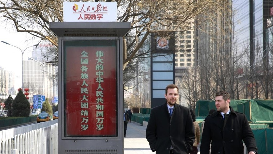 "Foreigners chat as they walk past a digital display board stating ""Long live the great People's Republic of China, Long live the great unity of all ethnic groups"" by China's state media on display in Beijing Monday, March 2, 2015. In the two-plus years since President Xi Jinping took the helm of the ruling Communist Party, state media have  become more strident in defending the one-party system and stoking nationalism. (AP Photo/Andy Wong)"