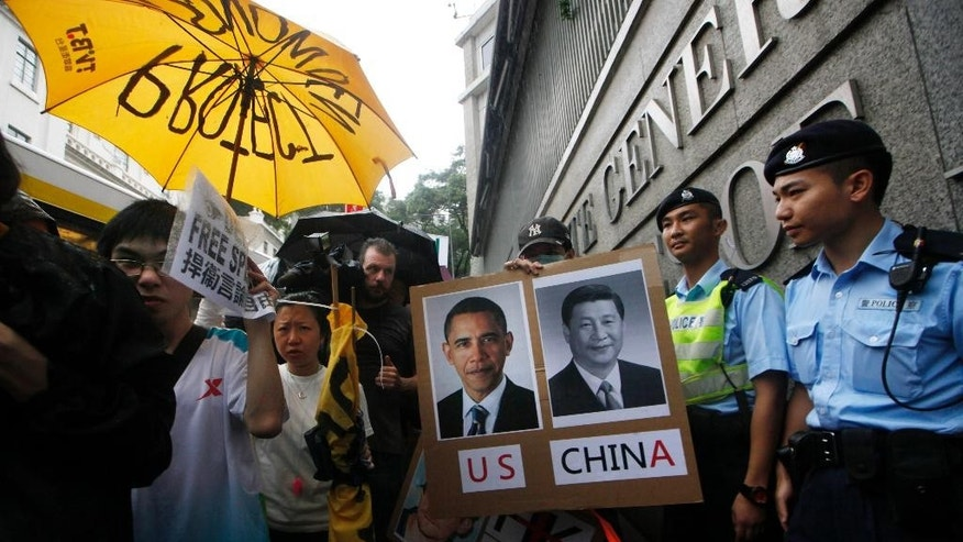 FILE - In this June 15, 2013 photo, supporters of NSA leaker Edward Snowden hold portraits of U.S. President Barack Obama, left, and Chinese President Xi Jinping during a demonstration outside the Consulate General of the United States in Hong Kong, accusing the U.S. government of infringing people's rights and privacy. In the two-plus years since President Xi Jinping took the helm of the ruling Communist Party, state media have become more strident in defending the one-party system and stoking nationalism. (AP Photo/Kin Cheung, File)