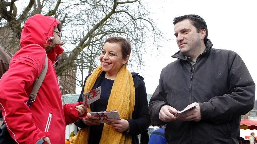 In this picture taken Sunday, March 1, 2015, Fatiha Ihallaine, 45, center, and Francis Andre, 45, right, candidates of French Socialist Party, campaign at an open market in Lille, northern France. In France's upcoming local elections, one thing is certain: Women will win half the seats. After years of largely failed efforts to get more women in politics, electoral officials devised a new rule for March 22 and March 29 elections for 4,108 local council members around France.(AP Photo/Michel Spingler)