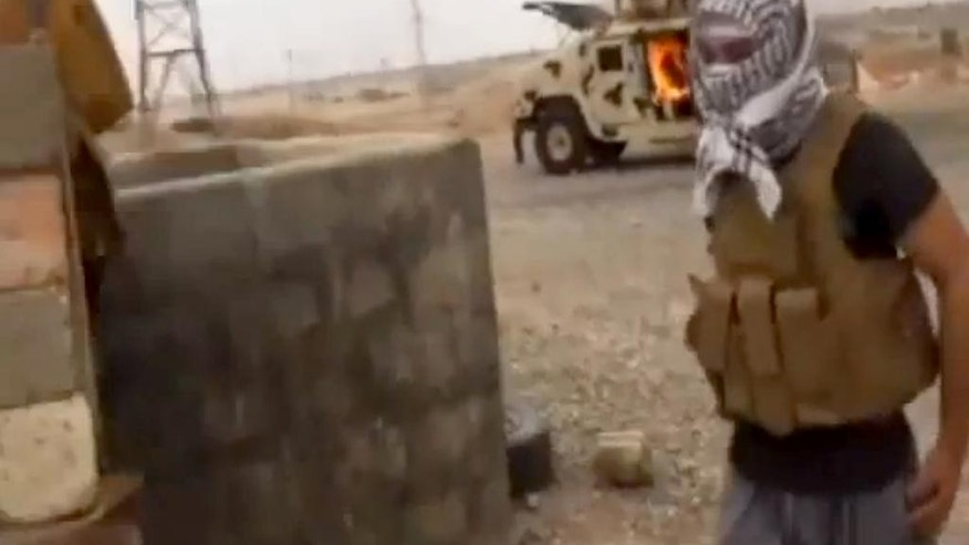 FILE - This image made from video posted by Iraqi0Revolution, a group supporting the al-Qaida breakaway Islamic State of Iraq and the Levant (ISIL) on Wednesday, June 11, 2014, which has been verified and is consistent with other AP reporting, shows a militant standing in front of a burning Iraqi Army Humvee in Tikrit, Iraq. The success - or failure - of the latest effort to retake Saddam Hussein's hometown will serve as a test for Iraqi forces and powerful Shiite militias as they prepare to launch major operations to take back northern Iraq. But challenges remain for Iraq's embattled military which is still working to recover losses suffered during the Islamic State's initial onslaught last year. (AP Photo/Iraqi0Revolution, File)