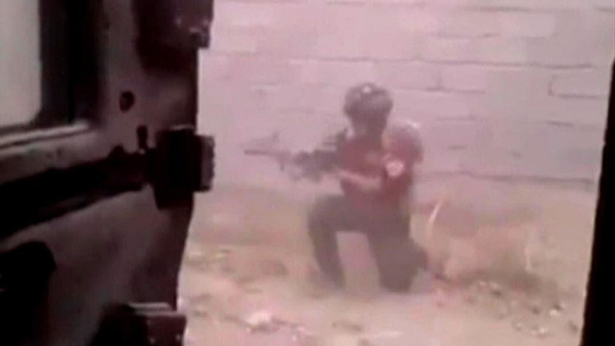 FILE - This file image made from video provided by an Iraqi soldier made available on Saturday, June 14, 2014, shows a member of Iraqi Special Operations forces in a firefight with militants from the al-Qaida inspired Islamic State of Iraq and the Levant (ISIL), later known as the Islamic State group, in Tikrit, Iraq. The success - or failure - of the latest effort to retake Saddam Hussein's hometown will serve as a test for Iraqi forces and powerful Shiite militias as they prepare to launch major operations to take back northern Iraq. But challenges remain for Iraq's embattled military which is still working to recover losses suffered during the Islamic State's initial onslaught last year. (AP Photo/unofficial military handout via AP video, File)