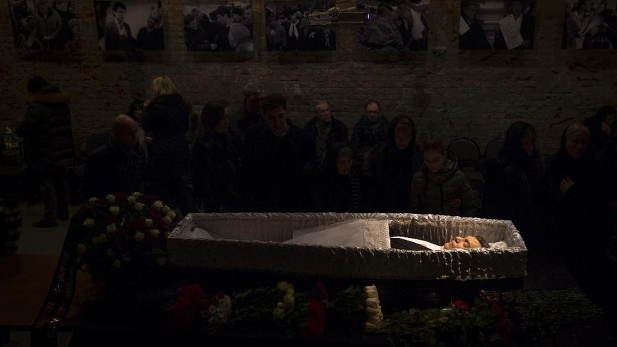Relatives and friends pay their last respects at the coffin of Boris Nemtsov, a charismatic Russian opposition leader and sharp critic of President Vladimir Putin, during a farewell ceremony inside the Sakharov's center in Moscow, Russia, Tuesday, March 3, 2015. Mourners are lining up outside the Moscow human rights center for the funeral of murdered Nemtsov. Western officials have called for Russia to conduct a prompt, thorough, transparent and credible investigation into the slaying. Putin has ordered law enforcement chiefs to personally oversee the probe. (AP Photo/Pavel Golovkin)