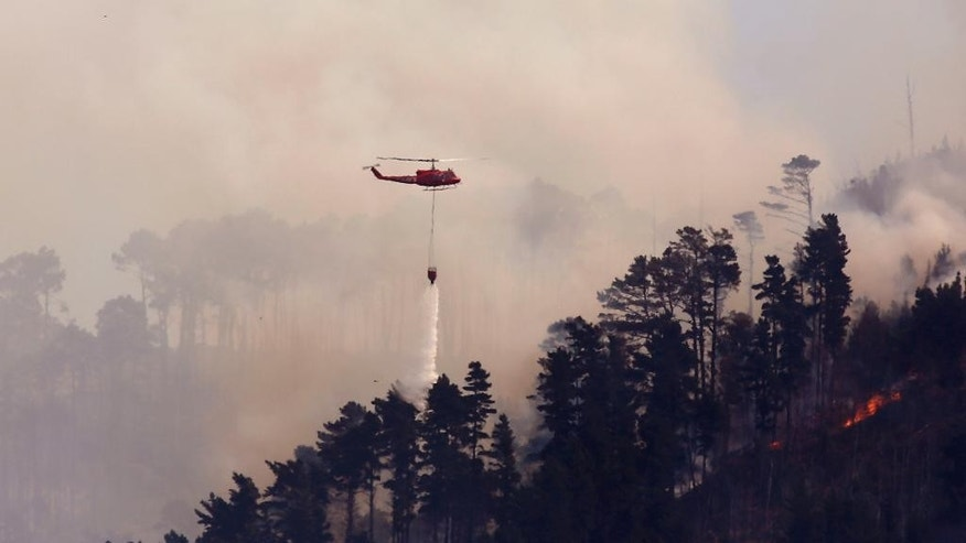 A helicopter drops water over a fire high up in a mountain on the outskirts of the city of  Cape Town, South Africa, Tuesday, March 3, 2015. South African firefighters say they are battling to control a wildfire's that has burned  homes in Cape Town's southern peninsula. (AP Photo/Schalk van Zuydam)