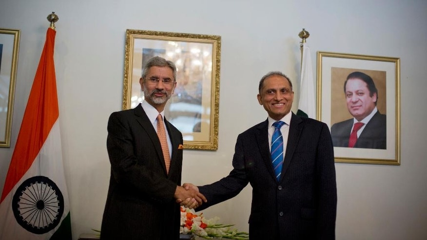 Indian Foreign Secretary Subrahmanyan Jaishankar, left, poses for photographers, as he shakes hands with his Pakistani counterpart Aizaz Chaudhry at the foreign ministry in Islamabad, Pakistan, Tuesday, March 3, 2015. India's foreign secretary has arrived in Pakistan on a two-day visit, marking the first high-level meeting since talks broke down between the two nuclear-armed rivals last year. (AP Photo/B.K. Bangash)