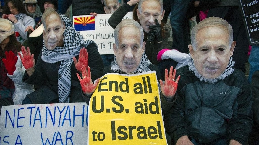 "Pro-Palestine demonstrators wearing Israeli Prime Minister Benjamin Netanyahu masks and symbolic ""blood stained hands,"" led by Code Pink, protest in front of the Washington Convention Center, where the 2015 American Israel Public Affairs Committee (AIPAC) Policy Conference is being held, in Washington, Sunday, March 1, 2015. (AP Photo/Cliff Owen)"