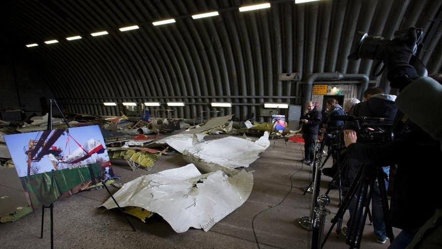 Journalists take images of parts of the wreckage of the Malaysia Airlines Flight 17 displayed in a hangar at Gilze Rijen airbase, Netherlands, Tuesday, March 3, 2015. The plane was brought down over conflict-torn eastern Ukraine on July 17, 2014 and Dutch investigators are still probing the cause of the crash that killed all 298 people on board. (AP Photo/Peter Dejong)