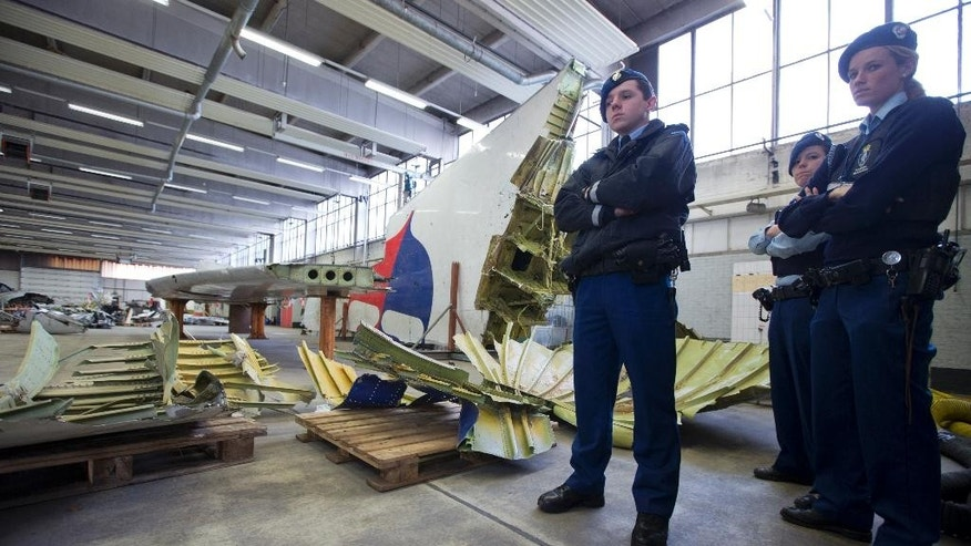 Dutch military police stands next to parts of the wreckage of the Malaysia Airlines Flight 17, displayed in a hangar at Gilze-Rijen airbase, Netherlands, Tuesday, March 3, 2015. The plane was brought down over conflict-torn eastern Ukraine on July 17, 2014 and Dutch investigators are still probing the cause of the crash that killed all 298 people on board. (AP Photo/Peter Dejong)