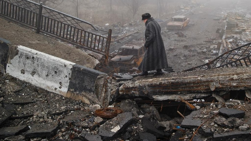 FILE - In this Sunday, March 1, 2015, file photo an elderly woman walks across a destroyed bridge, which has collapsed over the road to the airport, the scene of heavy fighting, in Donetsk, Ukraine.  (AP Photo/Vadim Ghirda, File)