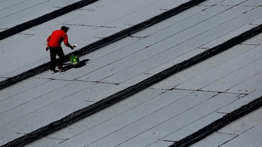 A man works on the insulation of a state school building's roof in the Athens suburb of Tavros,  on Tuesday, March 3, 2015. Greece' appears headed to re-enter recession this quarter, after starting to expand again last year following a punishing six-year recession that led to record-high joblessness. Unemployment remains the highest in the European Union, hitting 25.8 percent in November. (AP Photo/Petros Giannakouris)