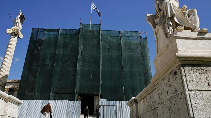 A Greek flag flies behind the statues of the ancient Greek philosopher Plato, front, and the goddess Athena as scaffolding covers the 19th Century Athens Academy building,  on Tuesday, March 3, 2015. Greece' appears headed to re-enter recession this quarter, after starting to expand again last year following a punishing six-year recession that led to record-high joblessness. Unemployment remains the highest in the European Union, hitting 25.8 percent in November. (AP Photo/Petros Giannakouris)