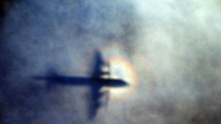 FILE - In this March 31, 2014 file photo, a ghostly shadow of a Royal New Zealand Air Force P3 Orion is cast on low level cloud while the aircraft searches for the missing Malaysia Airlines Flight 370 in the southern Indian Ocean, near the coast of Western Australia. Nearly a year has passed since Malaysia Airlines Flight 370 vanished on a flight from Kuala Lumpur to Beijing, sparking one of the most perplexing mysteries of modern times. Since then, search crews have taken to air, land and sea in a thus-far fruitless hunt for the plane and the 239 people who disappeared with it. (AP Photo/Rob Griffith, File)