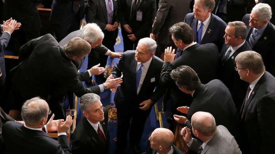 "Israeli Prime Minister Benjamin Netanyahu shakes hands as he leaves the House chamber on Capitol Hill in Washington, Tuesday, March 3, 2015, after addressing a joint meeting of Congress. In a speech that stirred political intrigue in two countries, Netanyahu told Congress that negotiations underway between Iran and the U.S. would ""all but guarantee"" that Tehran will get nuclear weapons, a step that the world must avoid at all costs. (AP Photo/Andrew Harnik)"