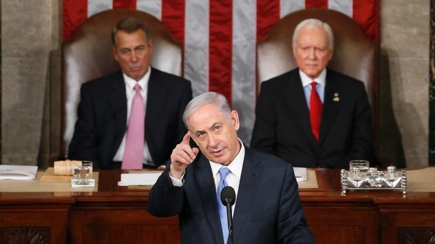 "Israeli Prime Minister Benjamin Netanyahu gestures as  he speaks before a joint meeting of Congress on Capitol Hill in Washington, Tuesday, March 3, 2015. In a speech that stirred political intrigue in two countries, Netanyahu told Congress that negotiations underway between Iran and the U.S. would ""all but guarantee"" that Tehran will get nuclear weapons, a step that the world must avoid at all costs. House Speaker John Boehner of Ohio, left, and Sen. Orrin Hatch, R-Utah, listen.  (AP Photo/Andrew Harnik)"