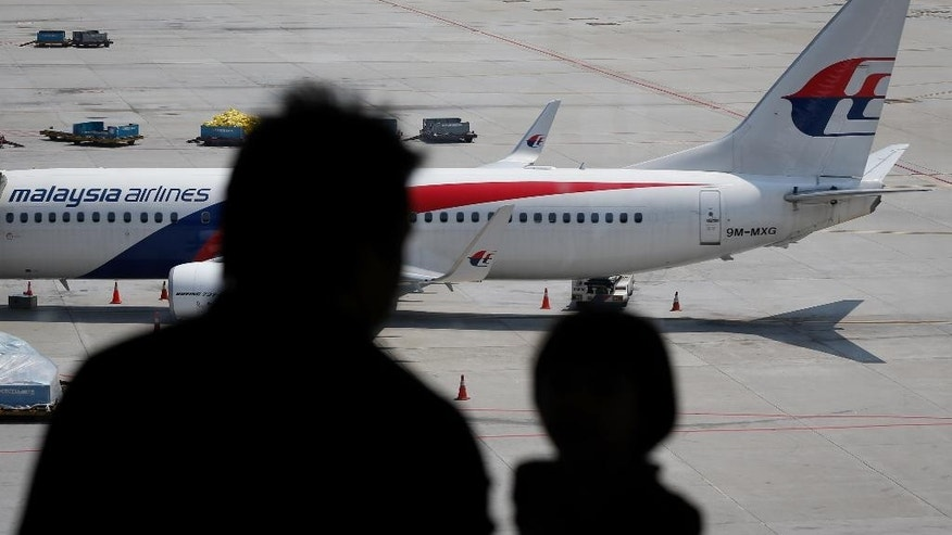 In this Friday, Feb. 27, 2015 photos, visitors look out from a viewing gallery as a Malaysia Airlines plane sits in the tarmac at the Kuala Lumpur International Airport (KLIA) in Sepang, Malaysia. After a year of unprecedented calamity for the Southeast Asian carrier,  Malaysia Airlines is aiming to return to profitability by 2017 with a drastic $1.7 billion overhaul that includes cutting nearly a third of its staff. (AP Photo/Vincent Thian)