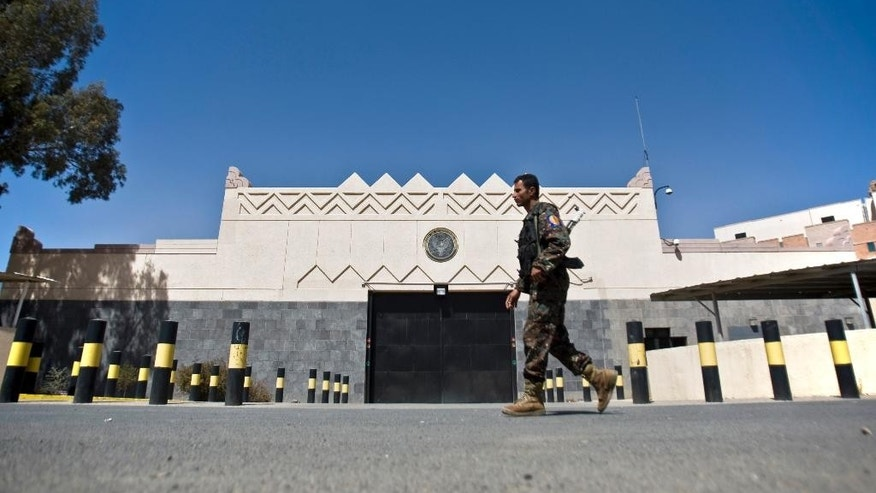 "A Houthi fighter wearing an army uniform, walks past the gate of the main entrance of the US embassy after Yemeni police opened the road in front of it in Sanaa, Yemen, Wednesday, March 4, 2015. Yemeni President Abed Rabbo Mansour Hadi called for the relocation of embassies to Aden, as several of the six-nation Gulf Cooperation Council members have done already. The U.S. ambassador to Yemen Matthew Tueller met with Hadi in Aden on Monday and said Hadi remained the ""legitimate"" leader of Yemen. (AP Photo/Hani Mohammed)"