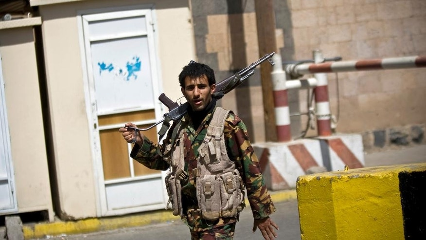 "A Houthi fighter wearing an army uniform, stands guard at the gate of the main entrance of the closed U.S. embassy after Yemeni police opened the road in front of it, in Sanaa, Yemen, Wednesday, March 4, 2015. Yemeni President Abed Rabbo Mansour Hadi called for the relocation of embassies to Aden, as several of the six-nation Gulf Cooperation Council members have done already. The U.S. ambassador to Yemen Matthew Tueller met with Hadi in Aden on Monday and said Hadi remained the ""legitimate"" leader of Yemen. (AP Photo/Hani Mohammed)"
