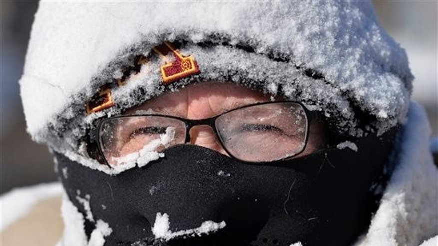 Milissa Preiss peers out from behind snow-covered glasses while clearing her Sartell, Minn., driveway Tuesday, March 3, 2015. A fast-moving storm dumped several inches of snow across the Upper Midwest on Tuesday, making travel treacherous in some areas and leading to at least several traffic-related fatalities. (AP Photo/The St. Cloud Times, Kimm Anderson)