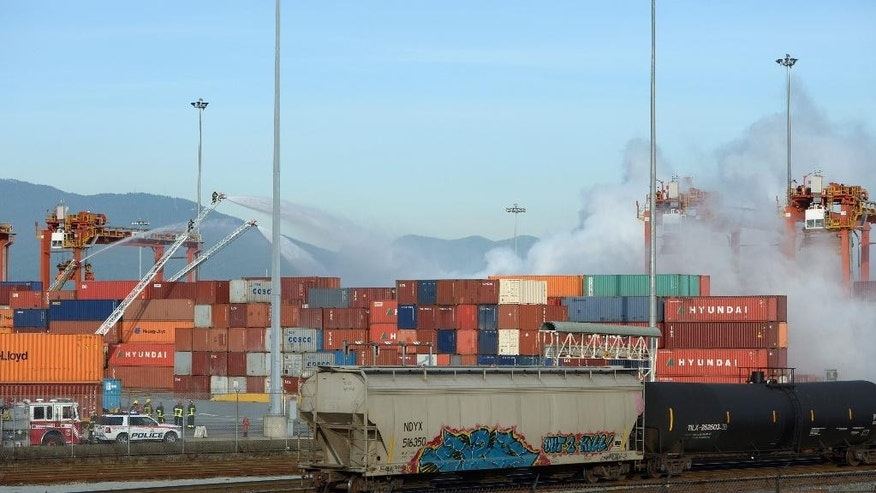 Firefighters pour water onto a fire at the Port Metro Vancouver in Vancouver, British Columbia, Canada, Wednesday, March 4, 2015. Vancouver health officials are warning people near the city's port to stay indoors due to a fire in the shipping container holding an industrial disinfectant and bleaching agent. (AP Photo/The Canadian Press, Jonathan Hayward)