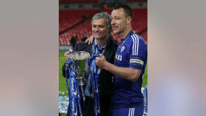 Chelsea's head coach Jose Mourinho, left and Chelsea's John Terry hold the trophy  after they won the English League Cup Final between Tottenham Hotspur and Chelsea at Wembley stadium in London, Sunday, March, 1, 2015. Chelsea won the match 2-0. (AP Photo/Tim Ireland)