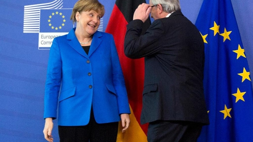 German Chancellor Angela Merkel, left, speaks with European Commission President Jean-Claude Juncker during her arrival at EU headquarters in Brussels on Wednesday, March 4, 2015. Chancellor Merkel is on a one day trip to Brussels to meet with the college of EU commissioners. (AP Photo/Virginia Mayo)