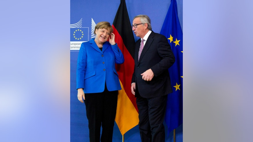 German Chancellor Angela Merkel, left, speaks with European Commission President Jean-Claude Juncker during arrival at EU headquarters in Brussels on Wednesday, March 4, 2015. Chancellor Merkel is on a one day trip to Brussels to meet with the college of EU commissioners. (AP Photo/Virginia Mayo)