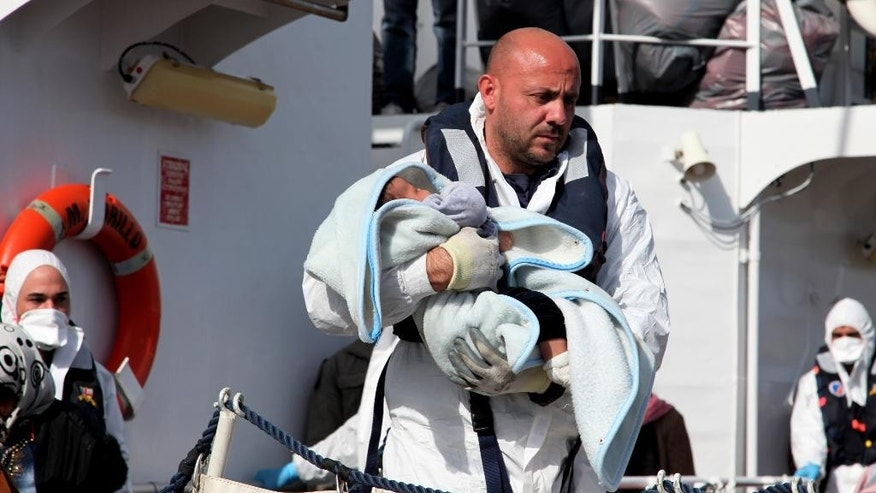 March 4, 2015: An officer carries a baby as migrants disembark from an Italian Coast Guard vessel after being rescued in Porto Empedocle, Sicily. (AP)