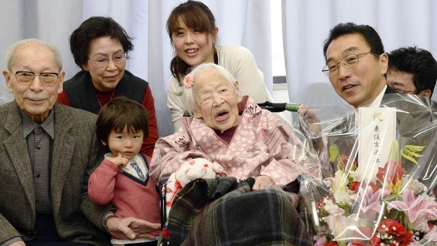 Japan's Misao Okawa, 116, center, who is recognized as the world's oldest living person by Guinness World Records, poses with her relatives and Ward Mayor Takehiro Ogura, right, as she is celebrated at a nursing home in Osaka, western Japan Wednesday, March 4, 2015 ahead of her birthday.  Okawa will turn 117 on Thursday, March 5. (AP Photo/Kyodo News) JAPAN OUT, MANDATORY CREDIT