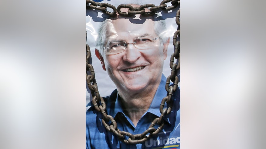 FILE - In this Feb. 20, 2015 file photo, a supporter of Caracas Mayor Antonio Ledezma holds a poster of him with chains during a protest against his arrest for allegedly plotting to overthrow the government of President Nicolas Maduro in Caracas, Venezuela. Ledezma's step daughter Isabel Gonzalez is married to government official Andres Izarra. Shortly after the mayor's arrest, attention turned to Izarra and whether family loyalty would trump ideological zeal. (AP Photo/Alejandro Cegarra, File)