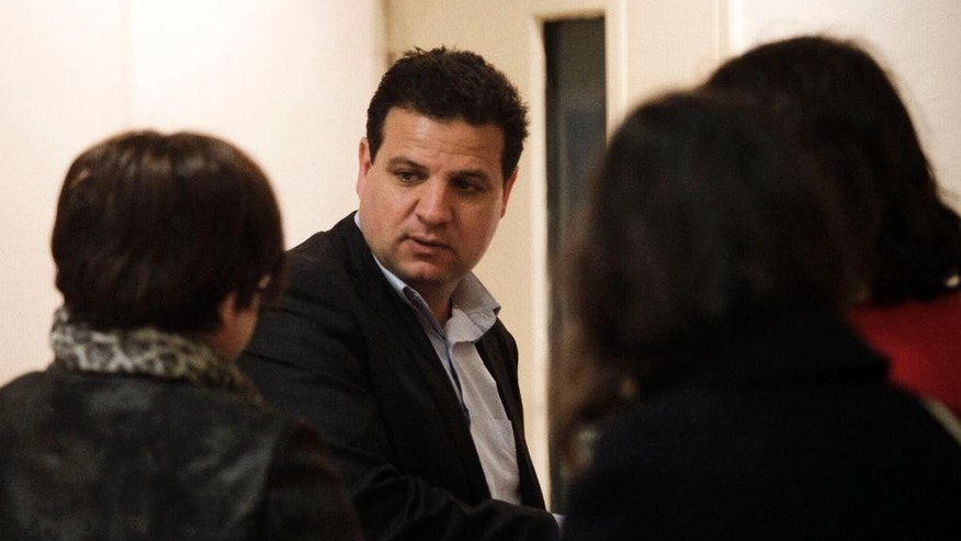 In this Monday, March 2, 2015 photo, Ayman Odeh, head of the Joint List, an alliance of four small Arab-backed parties running in the upcoming Israeli elections, talks to voters in Jerusalem. Odeh believes the unprecedented union of diverse groups will dramatically increase Arab clout in Israel's parliament and transform national politics. (AP Photo/Mahmoud Illean)