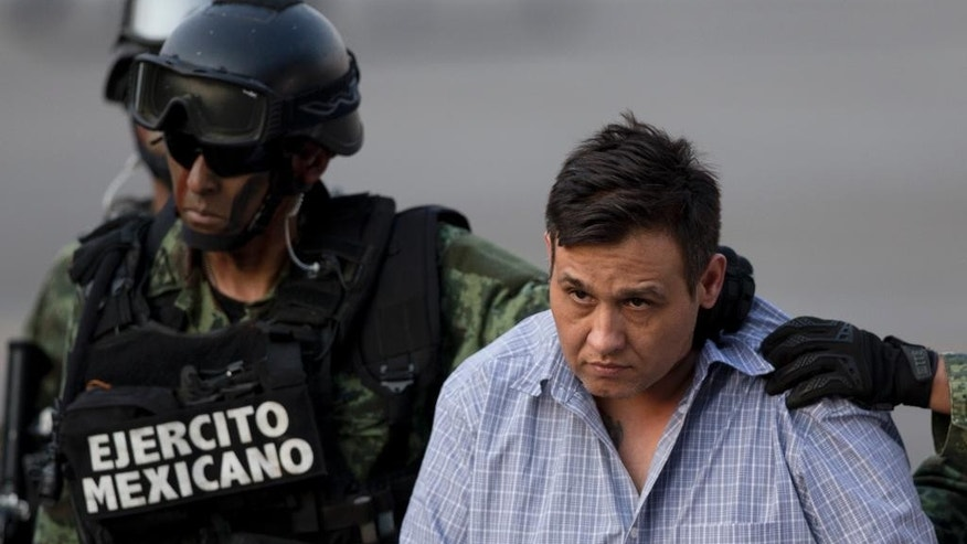 "A soldier escorts a man who authorities identified as Omar Trevino Morales, alias ""Z-42,"" leader of the Zetas drug cartel, at the Attorney General's Office hangar in Mexico City, Wednesday, March 4, 2015. An official who was not authorized to be quoted by name because of government policy, said Morales was arrested on Wednesday in a pre-dawn raid in San Pedro Garza Garcia, a wealthy suburb of the northern city of Monterrey. (AP Photo/Eduardo Verdugo)"