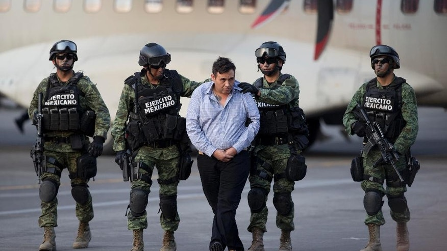 "Soldiers escort a man who authorities identified as Omar Trevino Morales, alias ""Z-42,"" leader of the Zetas drug cartel, as he is moved from a military plane to a military vehicle at the Attorney General's Office hangar in Mexico City, Wednesday, March 4, 2015. An official who was not authorized to be quoted by name because of government policy, said Morales was arrested on Wednesday in a pre-dawn raid in San Pedro Garza Garcia, a wealthy suburb of the northern city of Monterrey. (AP Photo/Eduardo Verdugo)"