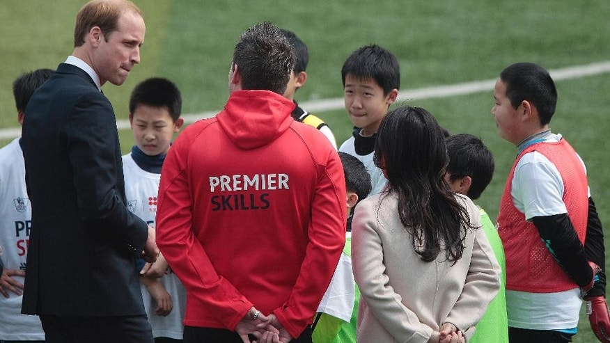 Britain's Prince William, left, meets with students as he attends the Premier Skills football coaching event at Nanyang Secondary School in Shanghai, China Tuesday, March 3, 2015. William focused his China trip on promoting links between the countries in football and film Tuesday, watching students kick balls around with Premier League-trained coaches ahead of a movie premiere. (AP Photo) CHINA OUT