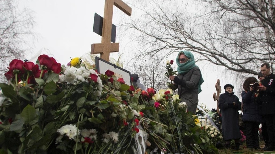 A woman lays flowers at the grave of Boris Nemtsov after a burial ceremony at Troekurovskoye cemetery in Moscow, Russia, Tuesday, March 3, 2015.  One by one, thousands of mourners and dignitaries filed past the white-lined coffin of slain Kremlin critic Boris Nemtsov on Tuesday, many offering flowers as they paid their last respects to one of the most prominent figures of Russia's beleaguered opposition. (AP Photo/Denis Tyrin)