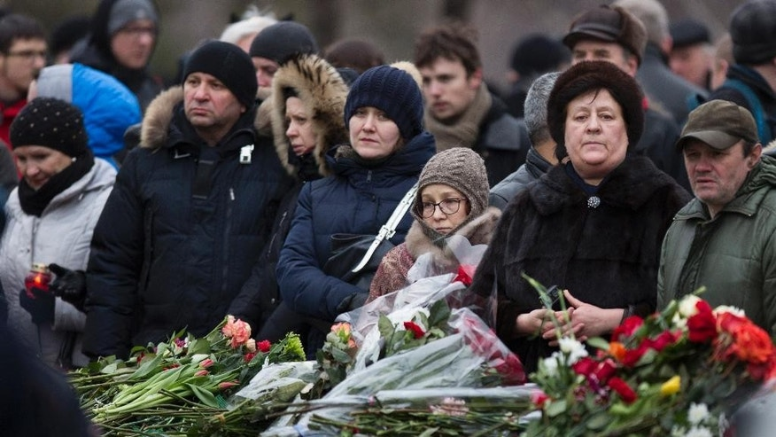 People stand at the coffin of Boris Nemtsov during a burial ceremony at Troekurovskoye cemetery in Moscow, Russia, Tuesday, March 3, 2015.  One by one, thousands of mourners and dignitaries filed past the white-lined coffin of slain Kremlin critic Boris Nemtsov on Tuesday, many offering flowers as they paid their last respects to one of the most prominent figures of Russia's beleaguered opposition. (AP Photo/Denis Tyrin)