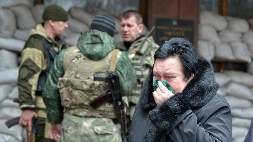 A woman reacts as she walks past pro-Russian rebels guarding the Zasyadko mine in Donetsk, Ukraine Wednesday March 4, 2015.  An explosion at the Zasyadko coal mine in war-torn eastern Ukraine killed 32 workers on Wednesday, the speaker of Ukraine's parliament said. Rebels who control the area, however, confirmed only one death. (AP Photo/Vadim Ghirda)