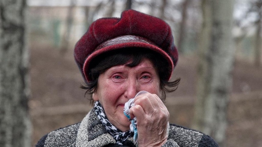 A woman cries as she waits to hear news about relatives after an explosion at  the Zasyadko coal mine in Donetsk, Ukraine Wednesday March 4, 2015.  An explosion at the Zasyadko coal mine in war-torn eastern Ukraine killed 32 workers on Wednesday, the speaker of Ukraine's parliament said. Pro-Russian rebels who control the area, however, confirmed only one death. (AP Photo/Vadim Ghirda)