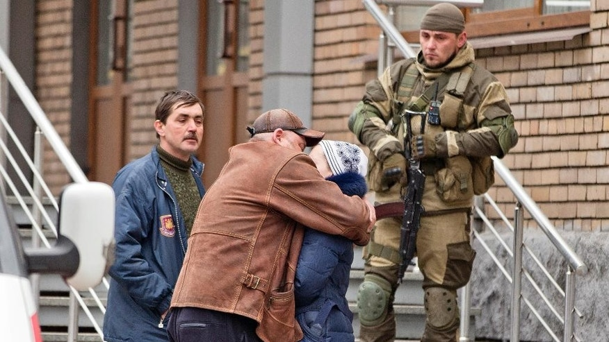 A pro-Russian rebel watches as people embrace as they wait to hear news about miners after an explosion at  the Zasyadko coal mine in Donetsk, Ukraine Wednesday March 4, 2015.  An explosion at the Zasyadko coal mine in war-torn eastern Ukraine killed 32 workers on Wednesday, the speaker of Ukraine's parliament said. Pro-Russian rebels who control the area, however, confirmed only one death. (AP Photo/Vadim Ghirda)